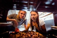 Γυναίκα που παίρνει τη μμένη πίτσα από τη σόμπα Στοκ Φωτογραφία