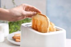Γυναίκα που παίρνει τη φέτα του ψωμιού από τη φρυγανιέρα Στοκ φωτογραφία με δικαίωμα ελεύθερης χρήσης