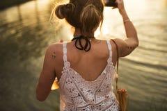 Γυναίκα που παίρνει τη φωτογραφία του ηλιοβασιλέματος από τη λίμνη Στοκ εικόνες με δικαίωμα ελεύθερης χρήσης