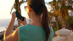 Γυναίκα που παίρνει τις εικόνες του ηλιοβασιλέματος στον περίπατο, Tenerife, Κανάρια νησιά, Ισπανία απόθεμα βίντεο