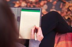 Γυναίκα που παίρνει τις σημειώσεις σε ένα μαξιλάρι Στοκ Φωτογραφία