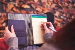 Γυναίκα που παίρνει τις σημειώσεις σε ένα μαξιλάρι Στοκ φωτογραφίες με δικαίωμα ελεύθερης χρήσης