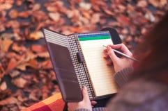 Γυναίκα που παίρνει τις σημειώσεις σε ένα μαξιλάρι Στοκ Εικόνες