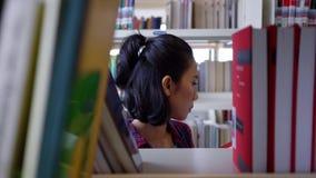 Γυναίκα που παίρνει το βιβλίο από το ράφι και διαβασμένος το απόθεμα βίντεο