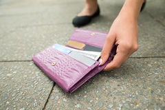 Γυναίκα που παίρνει το πεσμένο πορτοφόλι στοκ φωτογραφίες
