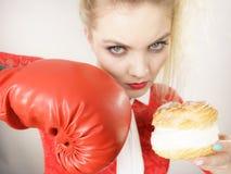Γυναίκα που παλεύει μακριά τα κακά τρόφιμα, που εγκιβωτίζουν το κέικ ριπών κρέμας Στοκ εικόνα με δικαίωμα ελεύθερης χρήσης