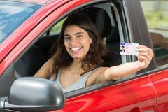 Γυναίκα που παρουσιάζει άδεια οδήγησής της στοκ εικόνα με δικαίωμα ελεύθερης χρήσης