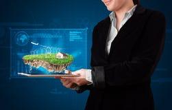 Γυναίκα που παρουσιάζει ένα τέλειο έδαφος οικολογίας με ένα σπίτι και windmil Στοκ Εικόνες