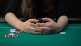 Γυναίκα που παρουσιάζει ζευγάρι άσσων και που παίρνει όλα τα τσιπ χαρτοπαικτικών λεσχών και τα χρήματα, νικητής παιχνιδιών απόθεμα βίντεο