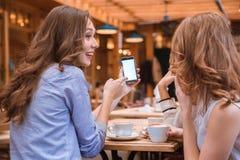 Γυναίκα που παρουσιάζει κάτι στην οθόνη smartphone στις φίλες της στοκ εικόνες