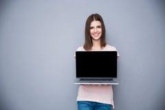 Γυναίκα που παρουσιάζει κενή οθόνη φορητών προσωπικών υπολογιστών Στοκ Φωτογραφία