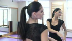 Γυναίκα που παρουσιάζει μετακίνηση χορού στο στούντιο κοντά στον καθρέφτη και την ξύλινη εγκάρσια ράβδο φιλμ μικρού μήκους