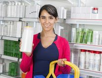 Γυναίκα που παρουσιάζει μπουκάλι σαμπουάν στο φαρμακείο στοκ εικόνα με δικαίωμα ελεύθερης χρήσης