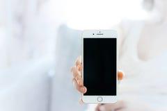 Γυναίκα που παρουσιάζει νέο iPhone 7 συν το smartphone Στοκ εικόνες με δικαίωμα ελεύθερης χρήσης