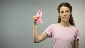 Γυναίκα που παρουσιάζει ρόδινη κορδέλλα στη κάμερα, διεθνής συνειδητοποίηση καρκίνου του μαστού απόθεμα βίντεο