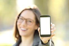 Γυναίκα που παρουσιάζει σας έξυπνη τηλεφωνική οθόνη υπαίθρια Στοκ Φωτογραφίες