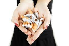 Γυναίκα που παρουσιάζει σπασμένα τσιγάρα υπό εξέταση Στοκ φωτογραφία με δικαίωμα ελεύθερης χρήσης