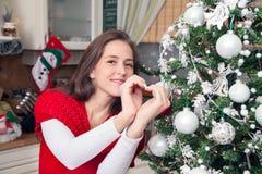 Γυναίκα που παρουσιάζει σύμβολο καρδιών στα Χριστούγεννα Στοκ Φωτογραφία