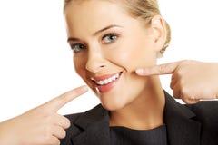 Γυναίκα που παρουσιάζει τέλεια άσπρα δόντια της στοκ φωτογραφία