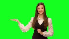 Γυναίκα που παρουσιάζει το προϊόν ή μήνυμά σας που χαμογελά ευτυχή που απομονώνεται στο πράσινο κλειδί χρώματος οθόνης Πράσινη δι απόθεμα βίντεο