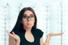 Γυναίκα που περιβάλλεται αναποφάσιστη από τα γυαλιά Eyeglasses στο κατάστημα Στοκ φωτογραφία με δικαίωμα ελεύθερης χρήσης