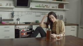 Γυναίκα που περιμένει το οινόπνευμα κατανάλωσης κλήσης στην κουζίνα απόθεμα βίντεο