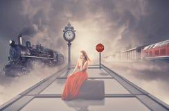 Γυναίκα που περιμένει το παλαιό τραίνο στην πλατφόρμα του σιδηροδρομικού σταθμού που μιλά στο τηλέφωνο Στοκ Εικόνες