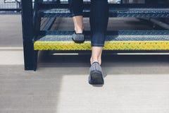 Γυναίκα που περπατά επάνω τα σκαλοπάτια μετάλλων Στοκ εικόνα με δικαίωμα ελεύθερης χρήσης