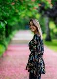 Γυναίκα που περπατά κάτω στην αλέα με τα δέντρα ανθών στοκ εικόνα