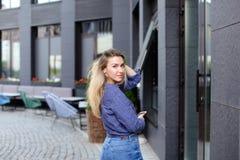 Γυναίκα που περπατά και που κρατά το smartphone στην πόλη Στοκ Εικόνες
