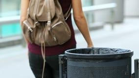 Γυναίκα που περπατά και που ρίχνει το gargage σε ένα δοχείο απορριμμάτων απόθεμα βίντεο