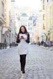 Γυναίκα που περπατά και που χρησιμοποιεί το έξυπνο τηλέφωνο στην οδό πόλεων Στοκ Εικόνες