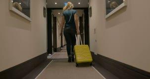 Γυναίκα που περπατά κατά μήκος της μετάβασης ξενοδοχείων με το καροτσάκι απόθεμα βίντεο