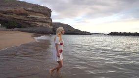 Γυναίκα που περπατά κατά μήκος της παραλίας απόθεμα βίντεο