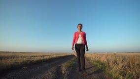 Γυναίκα που περπατά κατά μήκος του βρώμικου δρόμου την ηλιόλουστη ημέρα απόθεμα βίντεο