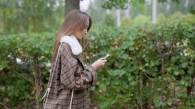 Γυναίκα που περπατά κοντά στους θάμνους και που χρησιμοποιεί το smartphone απόθεμα βίντεο