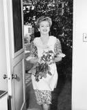 Γυναίκα που περπατά μέσω μιας πόρτας με τα λουλούδια στα χέρια της (όλα τα πρόσωπα που απεικονίζονται δεν ζουν περισσότερο και κα Στοκ Εικόνα