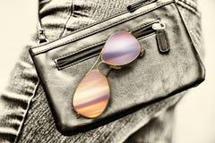 Γυναίκα που περπατά με ένα πορτοφόλι και τα γυαλιά ηλίου Στοκ φωτογραφία με δικαίωμα ελεύθερης χρήσης