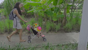 Γυναίκα που περπατά με το παιδί στο πάρκο του ξενοδοχείου απόθεμα βίντεο