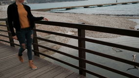 Γυναίκα που περπατά σε ένα ξύλινο κιγκλίδωμα γεφυρών και που αγγίζει τα δάχτυλά του φιλμ μικρού μήκους