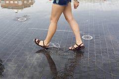 Γυναίκα που περπατά σε μια λακκούβα στην οδό στοκ φωτογραφίες με δικαίωμα ελεύθερης χρήσης