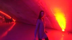 Γυναίκα που περπατά στα υπόγεια φω'τα νέου απόθεμα βίντεο