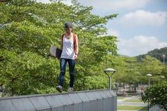 Γυναίκα που περπατά στην άκρη ενός αστικού τοίχου οικοδόμησης Στοκ φωτογραφία με δικαίωμα ελεύθερης χρήσης
