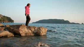 Γυναίκα που περπατά στην ακτή λιμνών, βήμα από τις πέτρες που εξετάζουν την απόσταση απόθεμα βίντεο