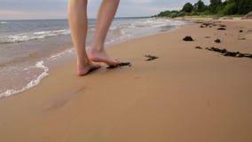 Γυναίκα που περπατά στην παραλία άμμου που αφήνει τα ίχνη στην άμμο απόθεμα βίντεο