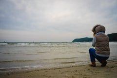 Γυναίκα που περπατά στην παραλία, κρύα ημέρα φθινοπώρου Στοκ φωτογραφία με δικαίωμα ελεύθερης χρήσης