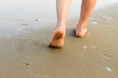 Γυναίκα που περπατά στην παραλία άμμου που αφήνει τα ίχνη στην άμμο clos Στοκ Φωτογραφία