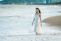 Γυναίκα που περπατά στην παραλία το καλοκαίρι Ευτυχές πολυφυλετικό ασιατικό κορίτσι που πηγαίνει στη θάλασσα Στοκ Φωτογραφίες