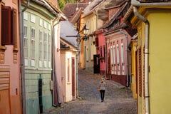 Γυναίκα που περπατά στη μεσαιωνική οδό σε SighiÈ™oara στοκ εικόνα