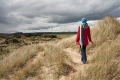 Γυναίκα που περπατά στους αμμόλοφους άμμου Στοκ Εικόνες